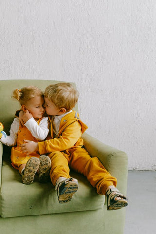 a boy and a girl cuddle in a green armchair