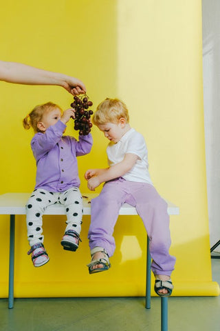 two young children wear matching colour unisex clothes holding a bunch of grapes