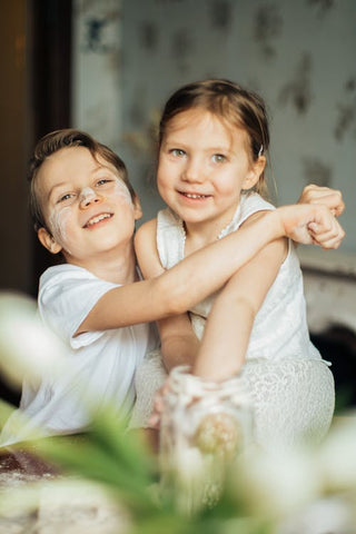 A brother and sister wearing white clothes hug
