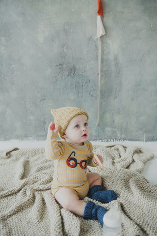 Baby wearing hand knitted baby clothes sitting on a blanket