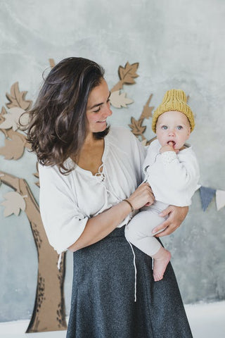 A woman carries a toddler child wearing unisex children's clothes and a knitted yellow hat