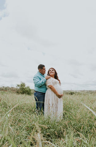 Pregnant woman in a white dress with her partner standing in a field