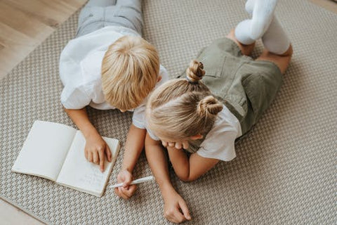 A boy and girl wear gender neutral clothing lay on the floor looking at a book