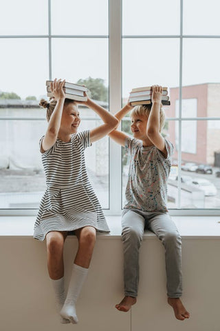 A boy and girl sit in the window with books on their heads