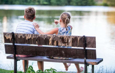 Boy and Girl sitting on a bench looking out to the water