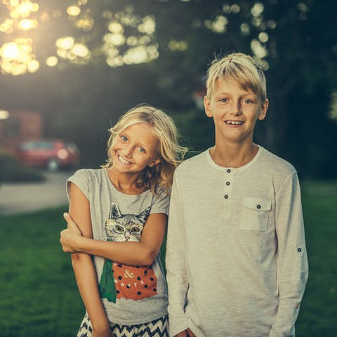 A boy and girl stood together outside smiling
