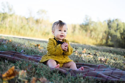 A baby girl in a yellow dress sits on a blanket on grass with leaves