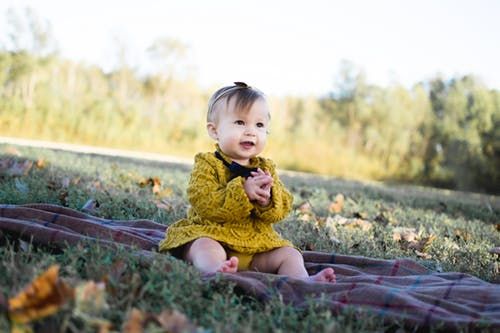 A baby girl wearing a yellow dress sits on a blanket laid on some grass
