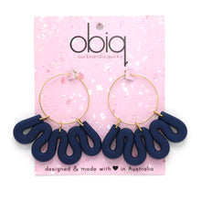 Load image into Gallery viewer, Gold hoop earrings with navy polymer clay squiggle hanging from hoop