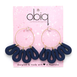 Gold hoop earrings with navy polymer clay squiggle hanging from hoop