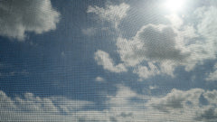 Window screen mesh with a view of fluffy white clouds and blue sky.