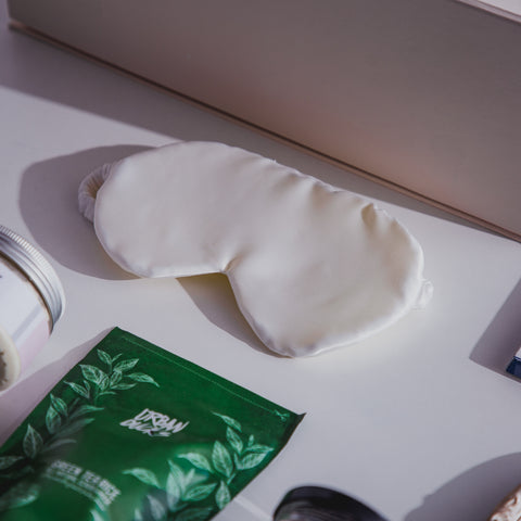 Picture of an eye mask surrounded by other recommended gift items