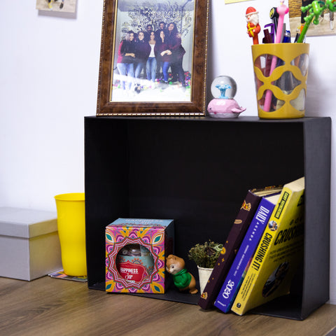 A living space with wooden floor and white wall showing a way to use giftopiia gift box as a storage space. A black giftopiia gift box is seen being used as a small box containing books, decorations, a toy, and more.