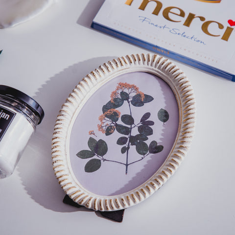 An oval picture frame with Merci dessert on top and a scented candle on the left.