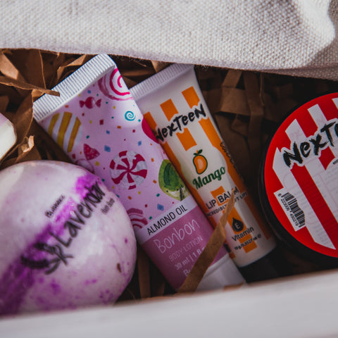 Collection of gifts inside a white gift box, with the body lotion and lip balm being the focus.