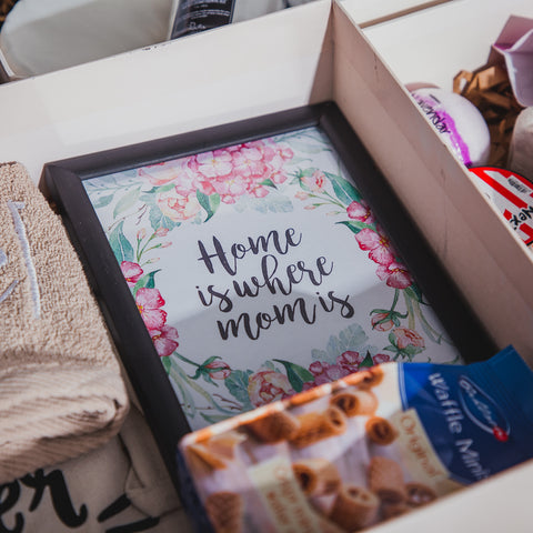 Collection of gift items in a white gift box with elegant picture frame being the focus