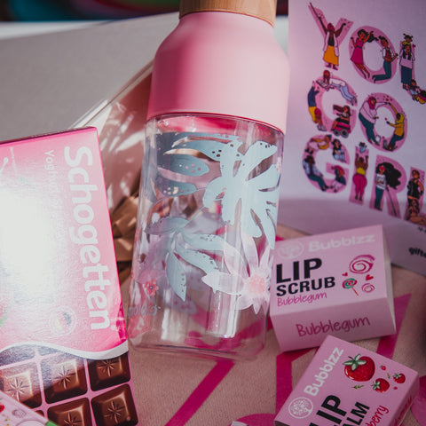 Collection of gift items in a white gift box with a pink water bottle being the focus.