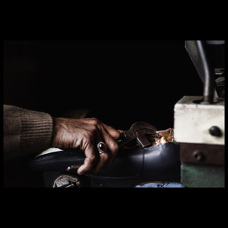 A craftsman closing a leather shoe upper.