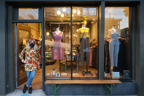 The Oakland storefront, with owner Hana leaning in the doorway and three dress forms in the windows, showing off Field Day clothing.