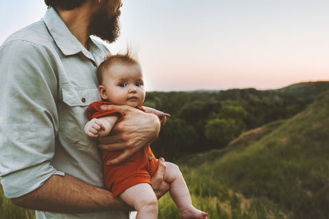 Man looking to the sunrise on the left while holding baby looking thats looking at the camera