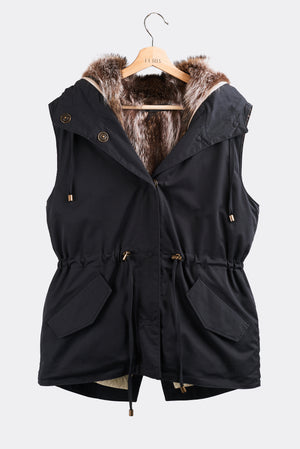 Classic and versatile vest with a detachable upcycled long hair or sheared racoon vest liner. The ultimate layering piece that can be worn across all seasons. Wear it sleek and straight or tighten the adjustable waist to enhance your figure. Fully lined with polyester quilted batt lining. Hand stitched Italian snaps and findings. Dry fast cotton polyester shell, a fish tail hem and stitched by hand. Hand made in Montreal.