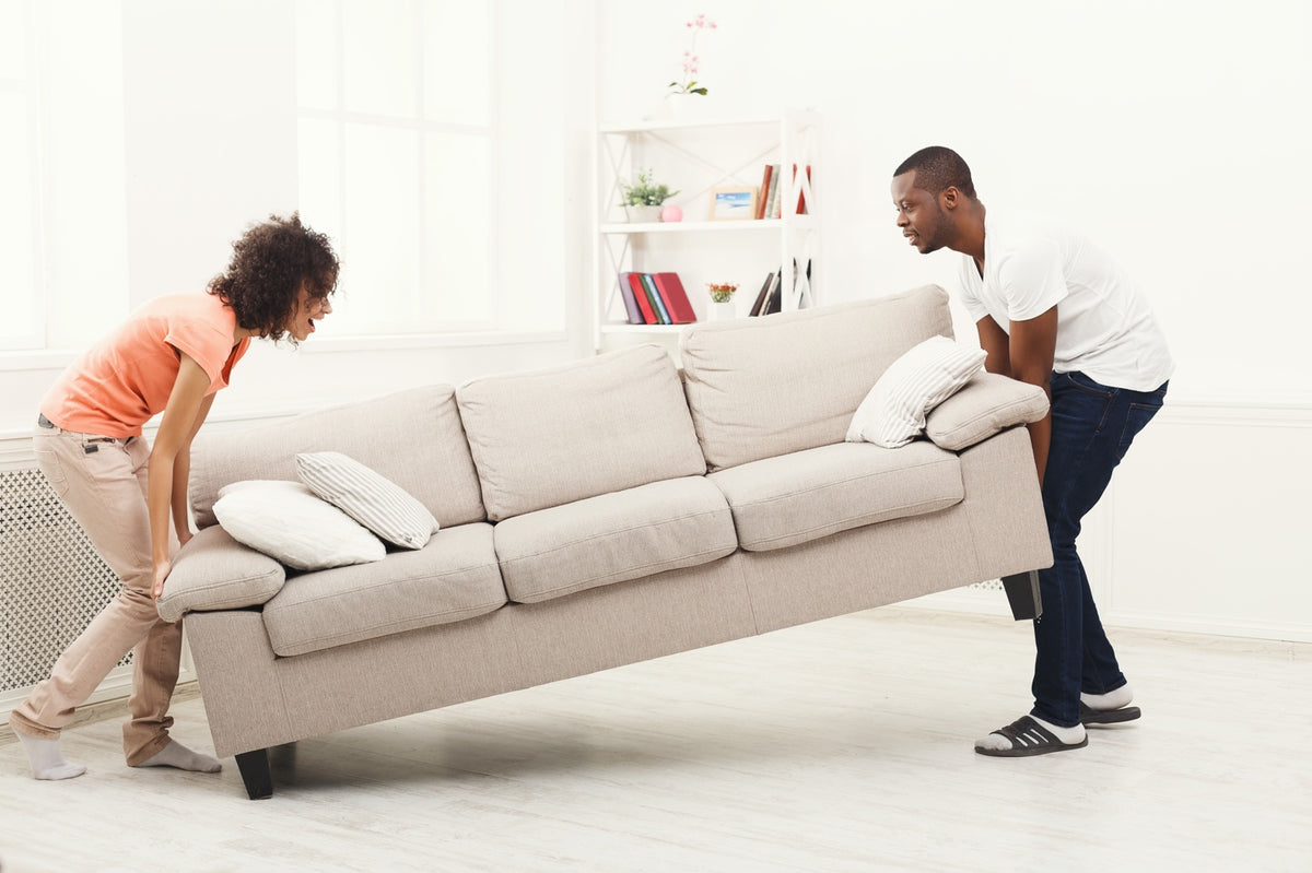 couple struggling to move heavy household furniture
