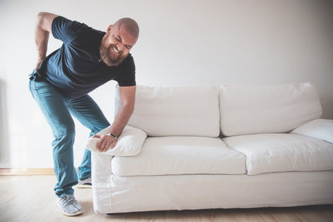 man with sore back from moving heavy household furniture