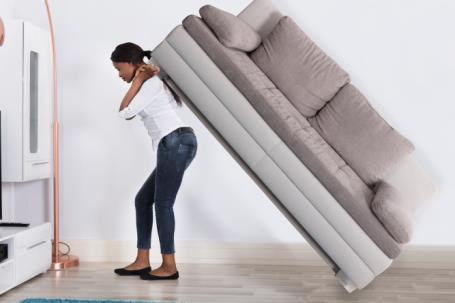 woman struggling to move heavy household furniture