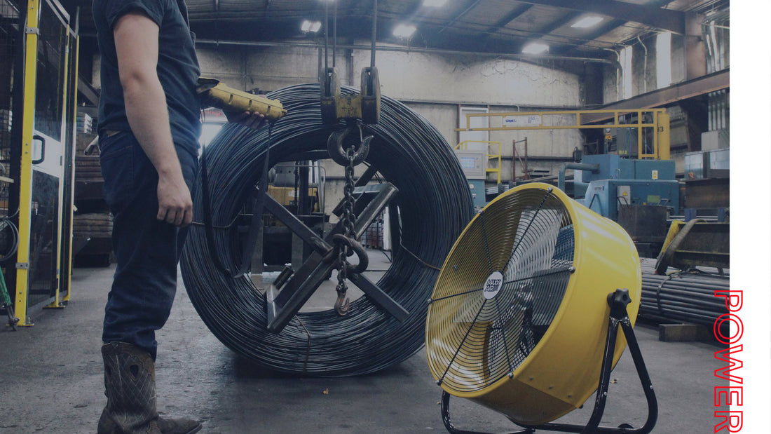 A BF24 drum fan spot cools an employee in a steel factory. The drum fan's portable design and heavy-duty steel housing make it an essential item in commercial, industrial, and warehouse operations for staff and employees to work comfortably.