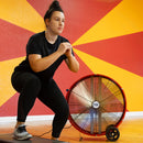 30 in. barrel fan cools woman working out in a gym.