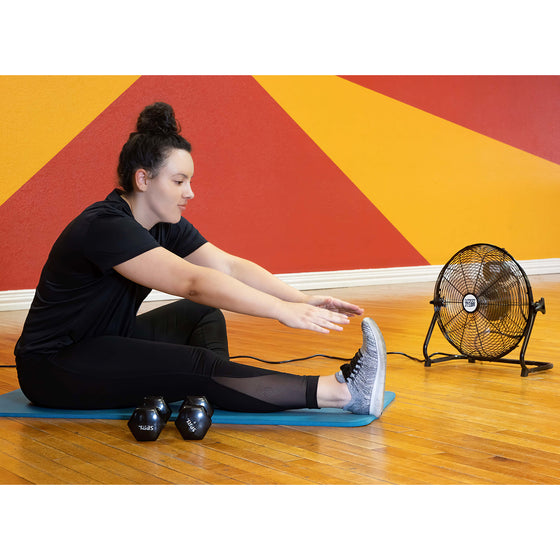 The 14 in. floor fan provides a refreshing breeze during a cool-down stretch at a fitness studio.