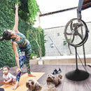 The 20 in. stand fan used outdoors on a home patio while a woman practices yoga around her child and pets.