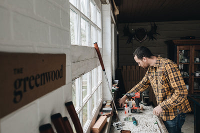 In wood shop where Greenwood handmade handcrafted solid wood golf putters are made, man in yellow plaid flannel in front of windows is reaching with his right arm over workbench where golf putter sits and sign to left reads the greenwood.