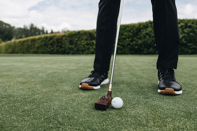 Solid wood putter in front of golfer's feet in black golf shoes. Handcrafted solid wood club head is resting on the putting green grass next to white golf ball.