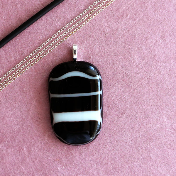 Medium-sized black fused glass pendant with white stripes, handmade.