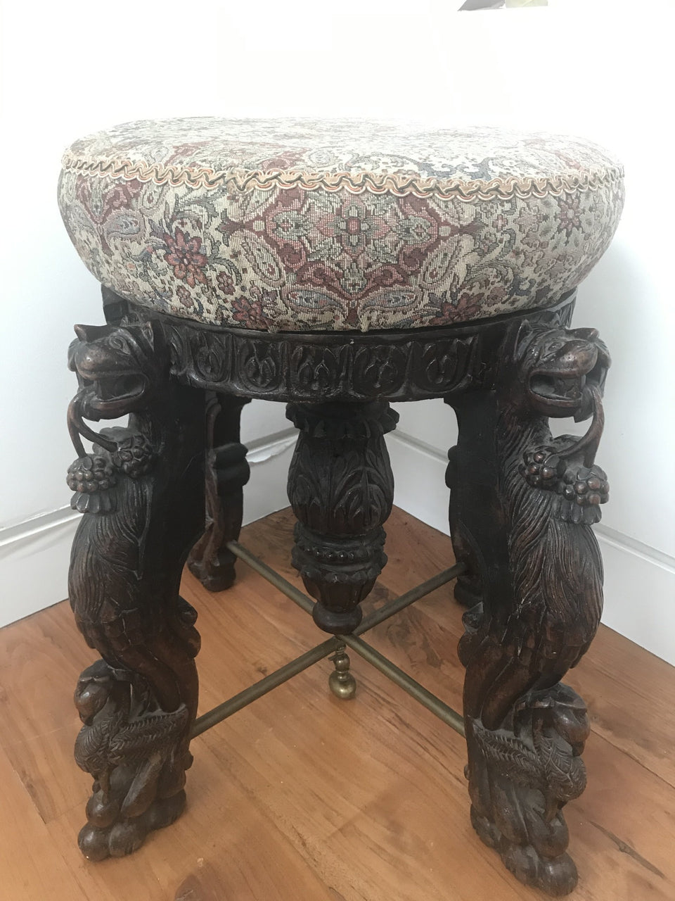 oriental stool with upholstered seat and four heavily carved legs with lions and birds and a carved centre column with brass stretchers