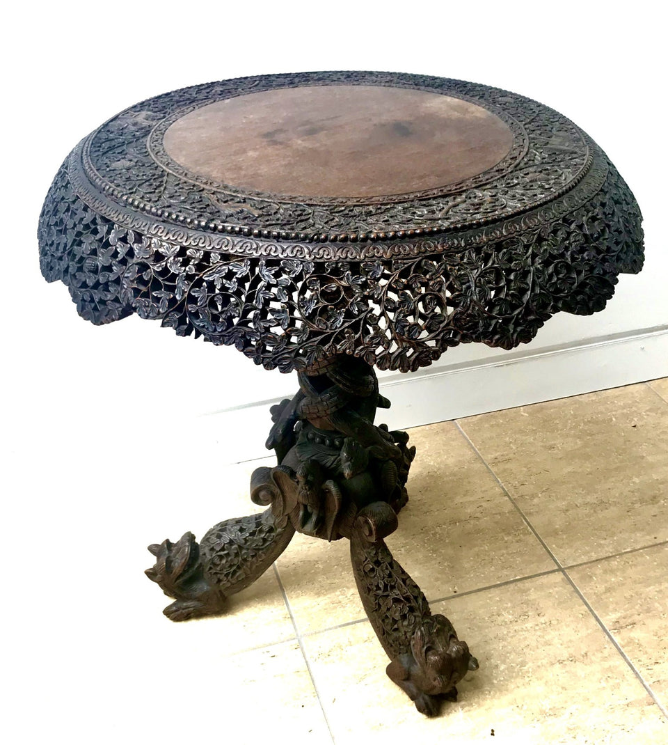 highly carved and pierced anglo-indian hardwood tilt top table with lions and snakes