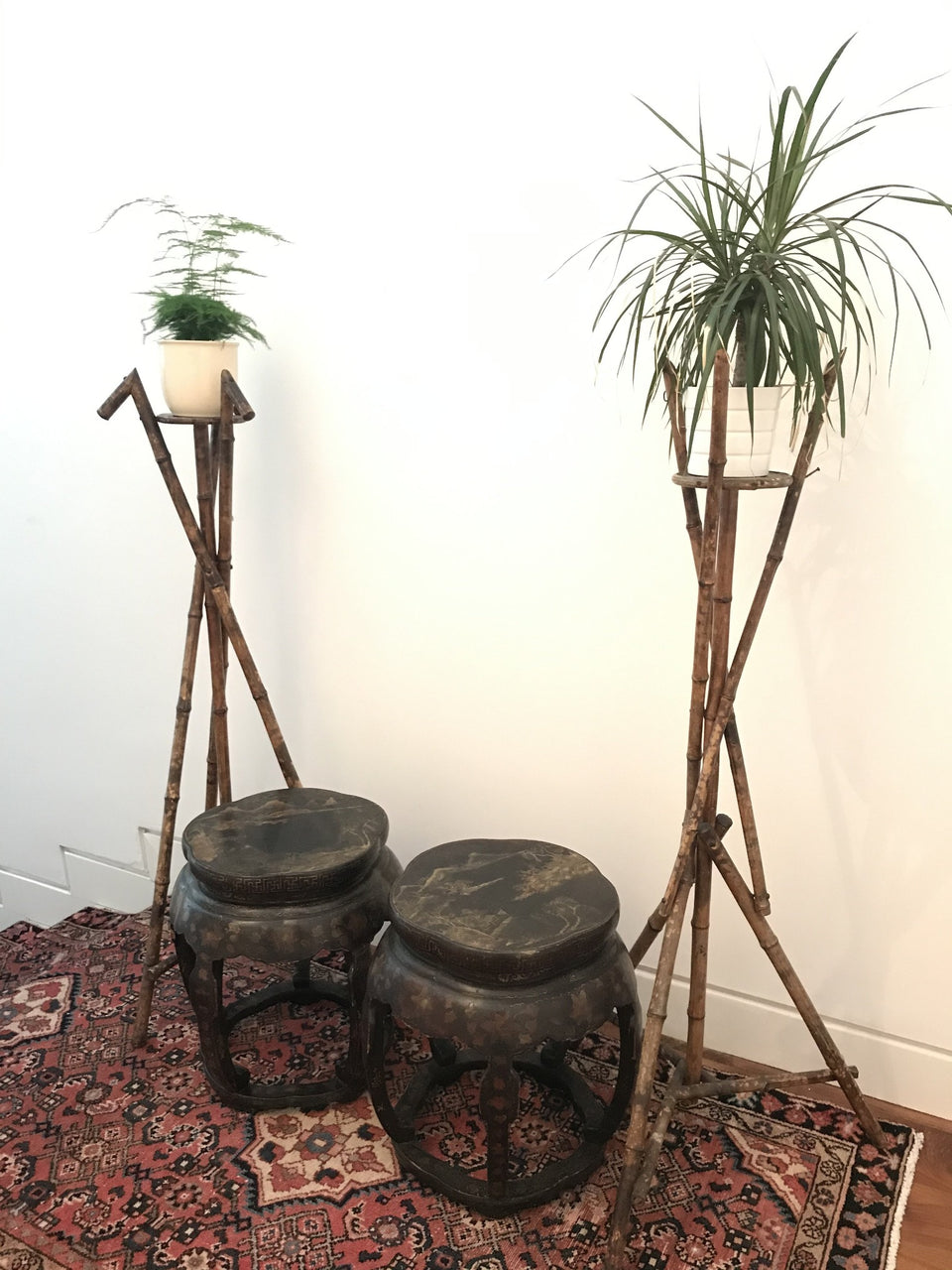 Antique Chinese lacquered stools beside a pair of Aesthetic Movement Victorian bamboo jardinieres