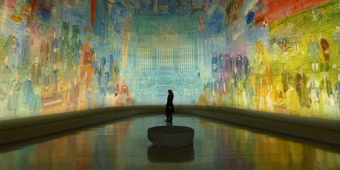 The silhouette of a person stands in the centre of a modern art museum surrounded by a giant abstract mural painted on the walls.