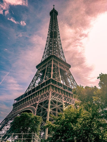 A beautiful angled shot of the Eiffel Tower with the sunset behind it shading the whole picture in tones of pink and purple