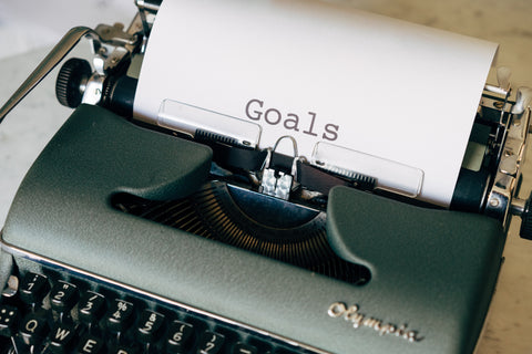 "A typewriter on a table, with a sheet of paper in the feeder. It reads ""Goals""."