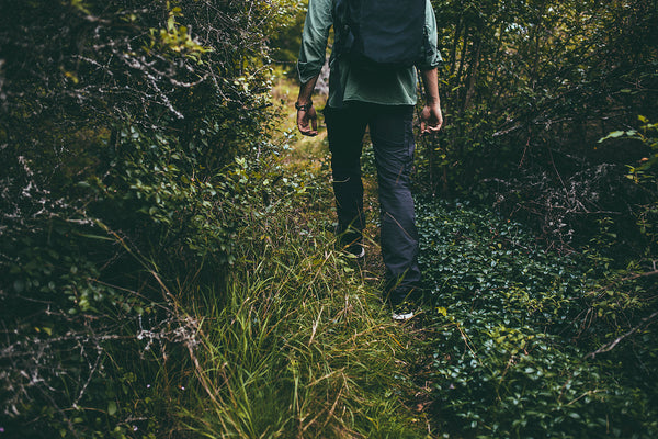 man walking in forest wearing black trousers and a black backpack