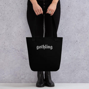 "A black tote bag with ""gothling"" written on it being held for scale."