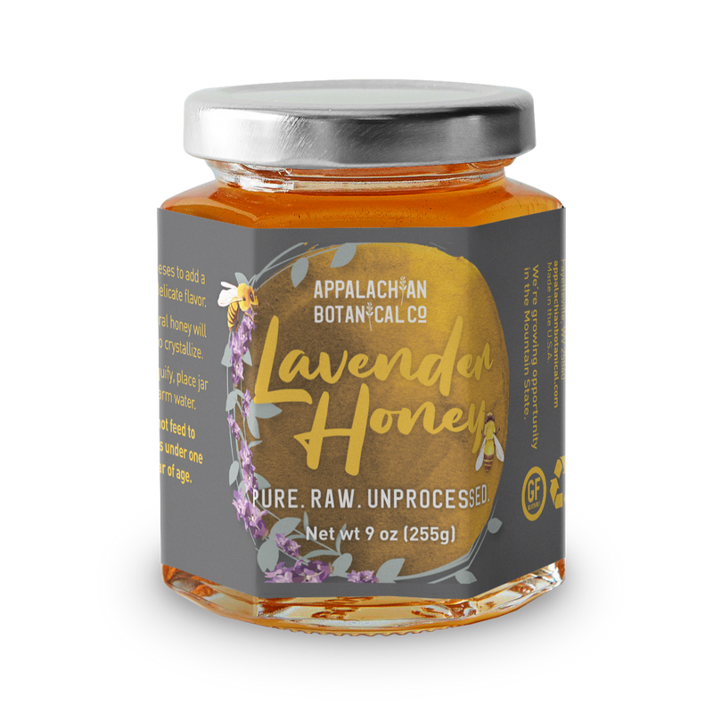 "Clear glass jar filled with honey. The jar has a silver, metal cap and a gray label. The label has a golden circle that is bordered by a lavender stalk and a bee on the left side. Inside the circle, the text ""Appalachian Botanical Co ; Lavender Honey ; Pure. Raw. Unprocessed ; Net wt 9 oz [255g]"" is printed. The text ""Lavender Honey"" is yellow with the image of a bee next to the 'y', while the rest of the text is white. Along the sides of the label, there is text printed in yellow that is unreadable."