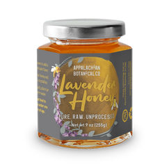 Clear glass jar filled with honey. The jar has a silver, metal cap and a gray label. The label has a golden circle that is bordered by a lavender stalk and a bee on the left side. Inside the circle, the text