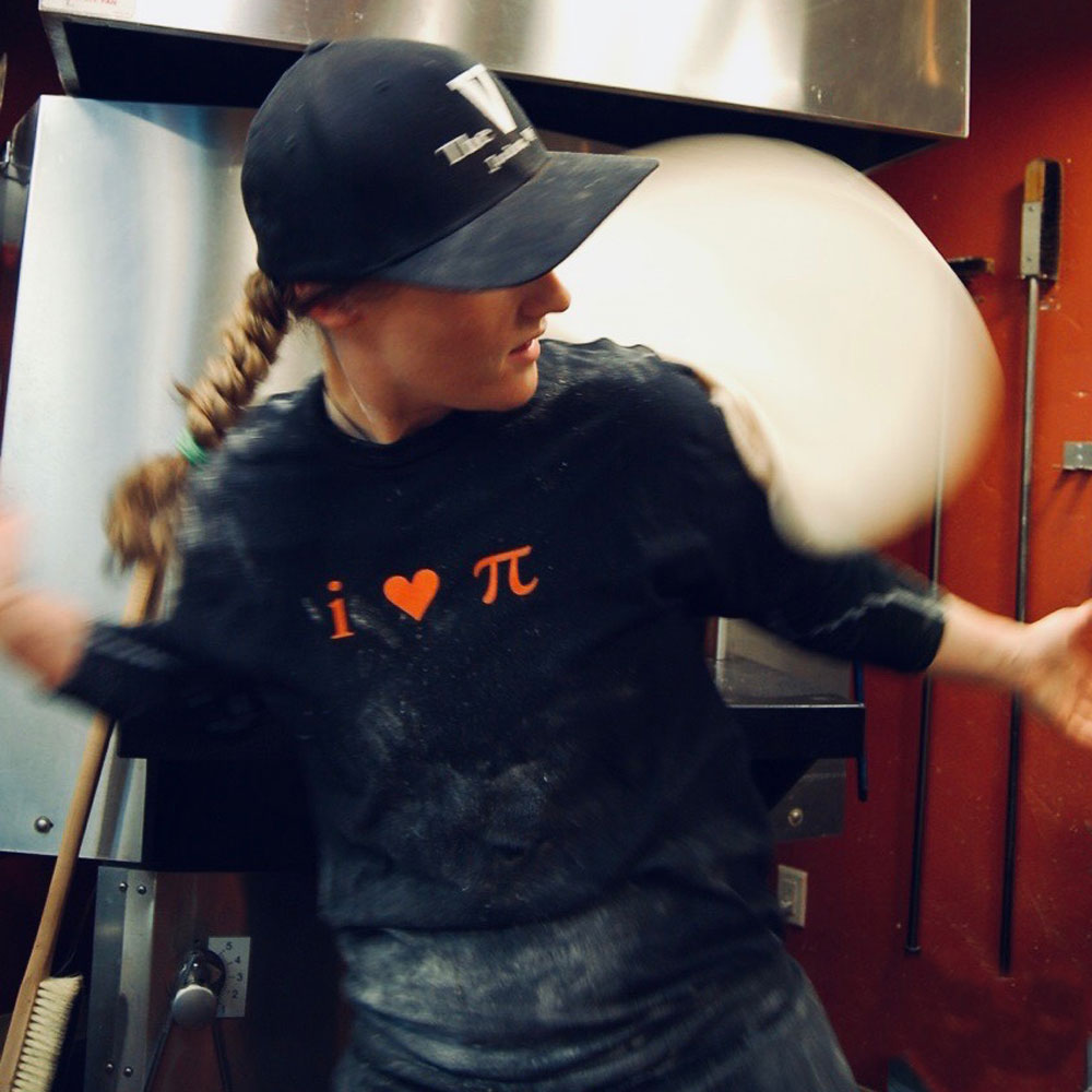 Katie denton, pizza master, tossing pizza behind her back