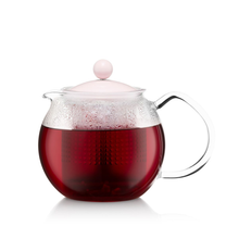 Load image into Gallery viewer, a glass tea press with a pink lid