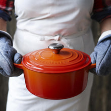 Load image into Gallery viewer, A cook holding the pot whilst wearing an apron and oven gloves