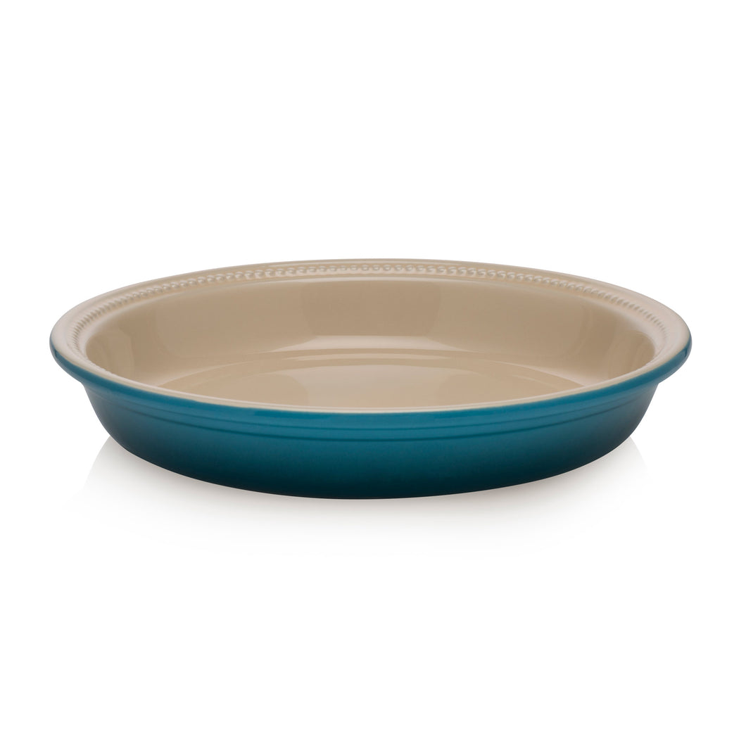 A pie dish with a blue ombre extrior and an beige interior