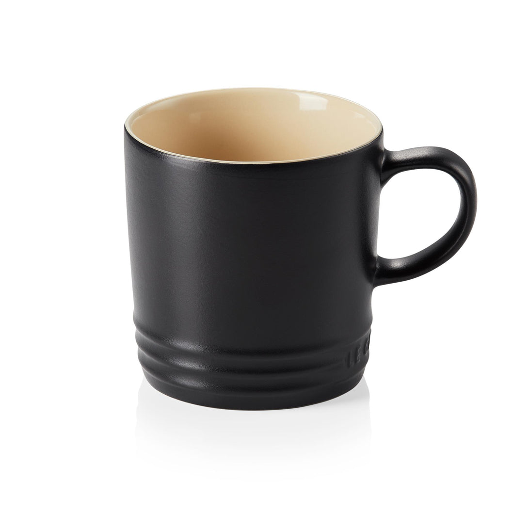 A black mug withy a handle and a beige interior